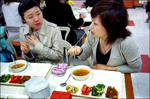 会社の食堂で同僚たちと昼食