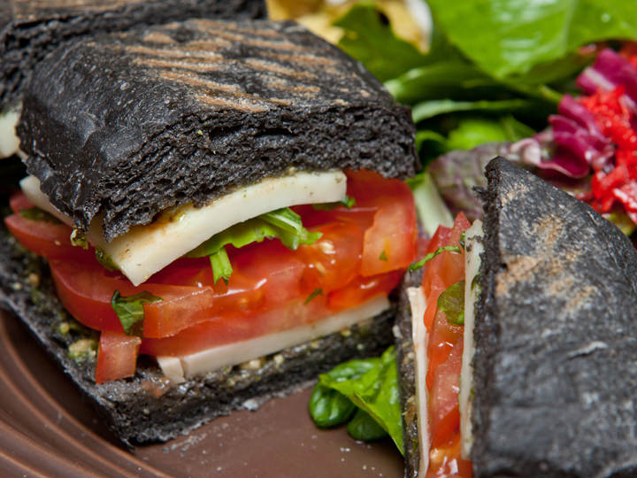 生地にイカ墨を練りこんだイタリアパンに、モッツァレラチーズとトマトをはさんだ「トマトパニーニ」