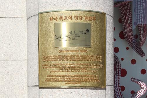 本店正面横の説明板は記念撮影スポットで、K-POPグループZE:Aのシワンも撮影