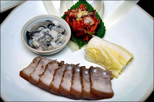 脂の乗った茹でた豚肉を白菜と牡蠣、キムチと一緒に食べます