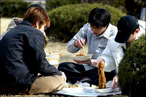 大学の校庭で食べる男子学生たち