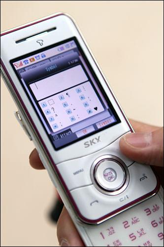 1.SMS作成欄で「記号(기호、Symbol)」を表示します。(ボタン式なら、カーソルを中心に右上のボタンをプッシュします。言語設定が韓国語なら1回、英語なら3回)