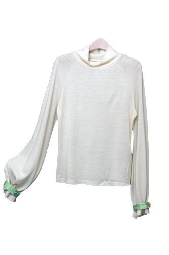 袖の形と、伝統生地を用いた飾りがおしゃれな白のタートルネック。(128,000ウォン)