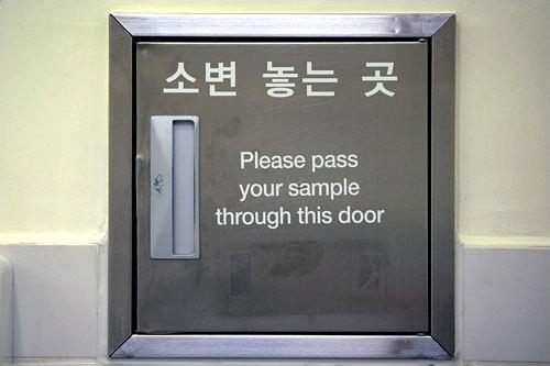 英語併記されたセンター内の設備(写真は尿検査提出口)
