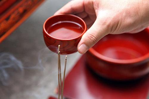祭主が線香の上で酒の入った杯を回す