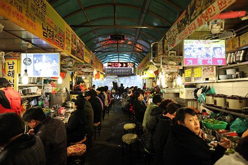 カルグッス横丁(地図:青10)メインストリート入ってすぐ、カルグッス(手打ち麺)専門店が10店舗ほど連なる。※外から見ると入口は暗く見えますが中に入るとお店は営業しています。