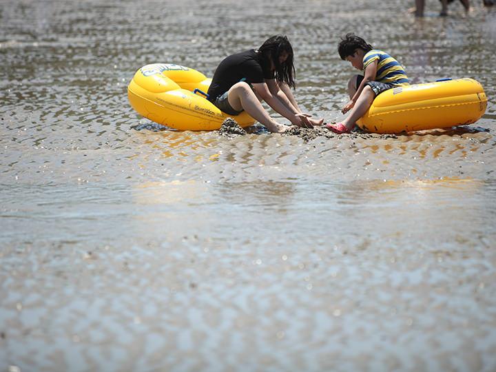 浮き輪に乗る子供ら