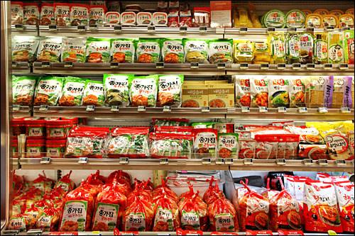スーパーのキムチコーナー。味も容量も多彩なキムチが並んでいる。
