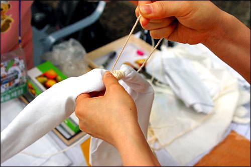 1. 布(綿)を用意し、黄土色に染めたくない個所を紐で縛ります。この時、黄土が染み込んでしまわないよう、固く縛ることが大切!