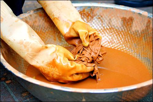 2. 黄土に水と塩を混ぜた液体に布を漬け、10分間揉みこみます。10分たったら強く絞ります。