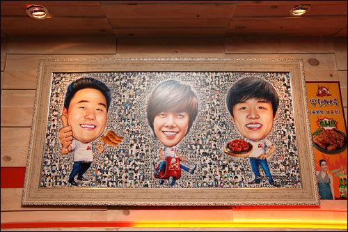 壁の中央に飾られた3人のイラスト。よく見ると背景はキム・ヒョンジュンの写真!