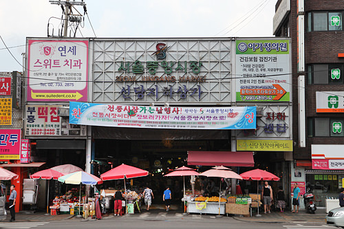 市場のメイン通り入口は新堂駅1番と2番出口の間に位置