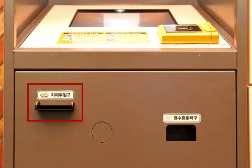 6-1.現金:紙幣を入れる(写真の赤線で囲まれている部分が紙幣投入口)。