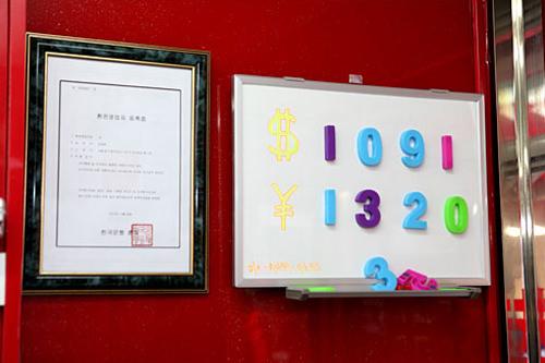 両替営業者登録証(写真左)とレートが掲げられている