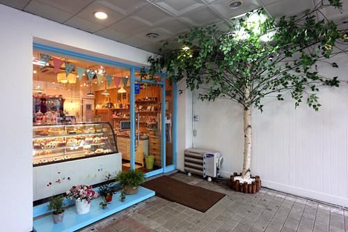 白い壁と水色の入り口がかわいらしいお店