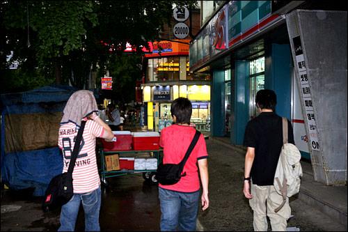雨の中カフェまで移動中の塩田さん(左)