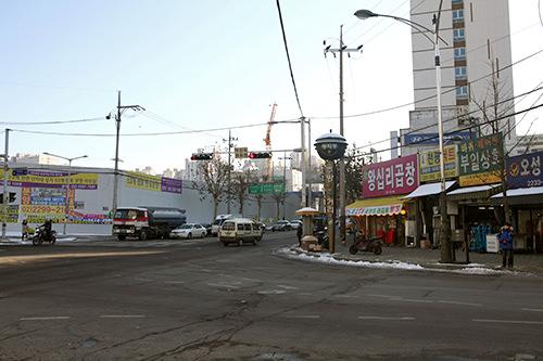 交差点の角に残る「往十里コプチャン」(写真右のピンクの看板)