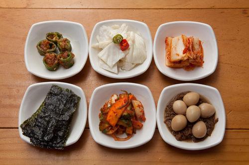 (左上から時計回りに)唐辛子の味噌漬け、キャベツのキムチ、白菜キムチ、牛肉と卵の煮つけ、キキョウの酢コチュジャン漬け、焼き海苔