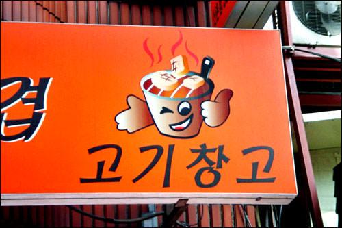 飲食店ではその店の柱を担う食材が指を立てているのが普通。しかしこの店はサムギョッサル屋さんで、指を立てているのは食べられる豚ではなく、焼く方の七輪。Good韓看の中では珍しいタイプ。