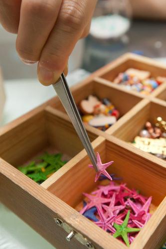 4.貝殻やサンゴ、ヒトデなどの装飾品をピンセットで入れます。
