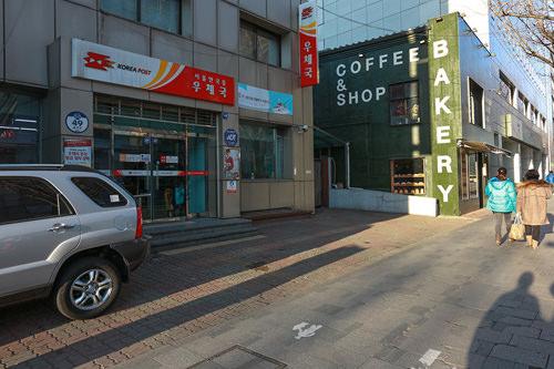 停留所の後ろは郵便局と緑色の外壁のベーカリー