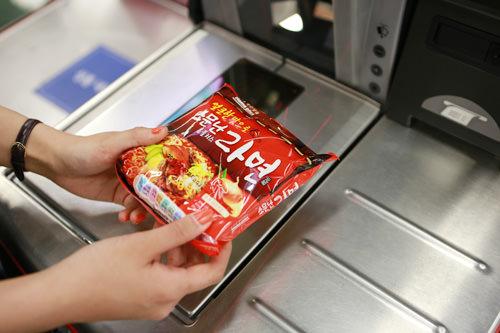 2.商品のバーコードを機械にスキャン。スキャンし終わった商品を左の台に置きます。