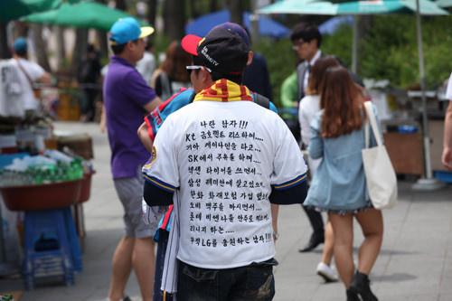 Tシャツの文字は「KIAの車に乗って、サムスンの家に住んでいるけど・・・俺はLGを応援する!」