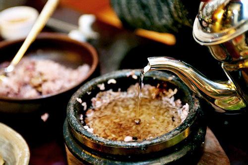 2.お焦げ(ヌルンジ)の残った釜に、「トブロハムッケ」特製のユリの根(トゥングルレ)茶を注ぎます。