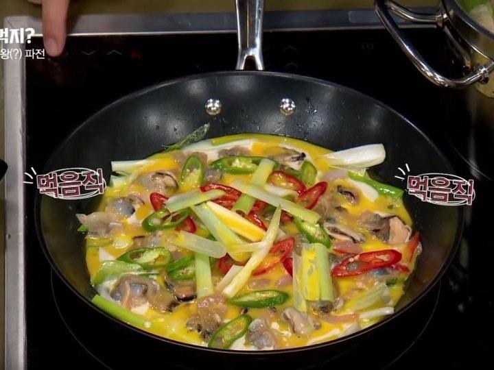 4.貝類と唐辛子をトッピングし、溶き卵をかける。中火で焼き、火が通ったら引っくり返す。