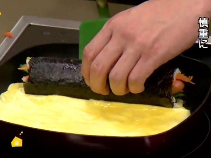 5.熱したフライパンに油を敷いて卵を流し入れ、卵に半分程火が通ったら海苔巻きを乗せて卵で包むように巻いていく
