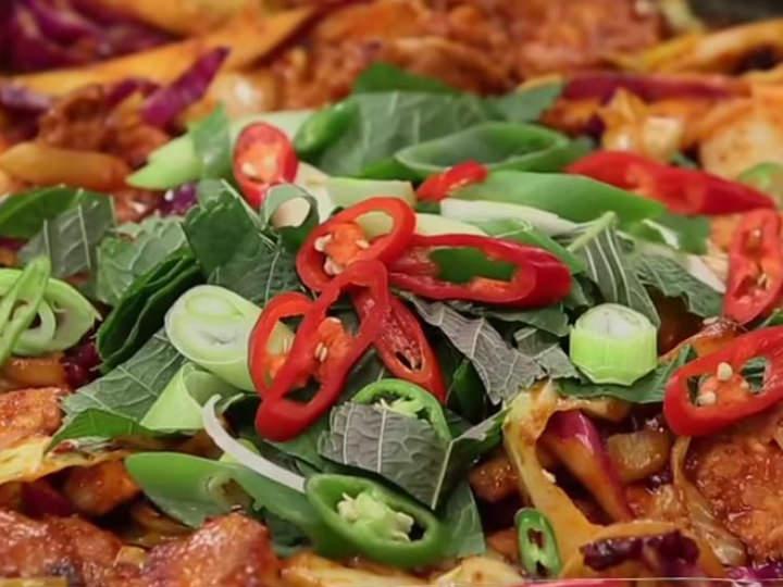 6. 熱した鉄板にサラダ油を敷き、鶏肉を入れて半分ほど火を通した後、キャベツ、紫キャベツ、タマネギ、サツマイモ、餅を加えて一緒に炒める。エゴマの葉と長ネギ、青唐辛子、赤唐辛子をのせて出来上がり